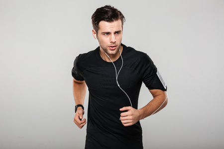 Portrait of a motivated confident man athlete in earphones listening to music while running isolated over gray background