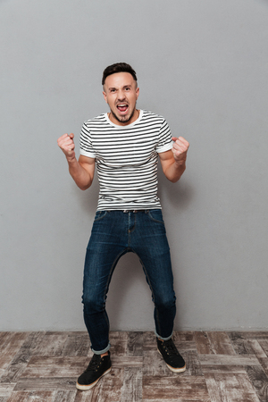 Full length portrait of a happy cheerful man celebrating success isolated over gray background