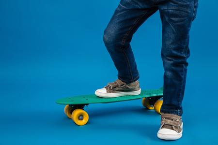 スケート ボード上の青色の背景やって来る若い男の子のトリミングされた画像 写真素材