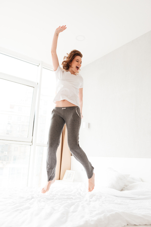 Image of happy amazing young woman in bed indoors jumping. Looking aside.