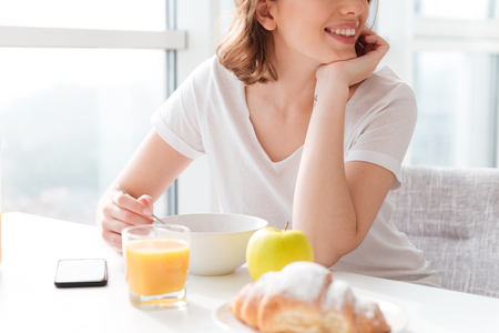 Cropped photo of cheerful young pretty woman sitting indoors at the table with juice and croissant.