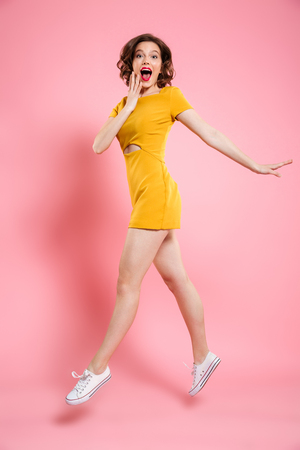 Full length portrait of happy exited woman in elegant yellow dress looking at camera while jumping over pink background