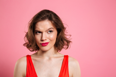 Close up portrait of a tricky pretty woman wearing bright make up looking away at copy space isolated over pink background