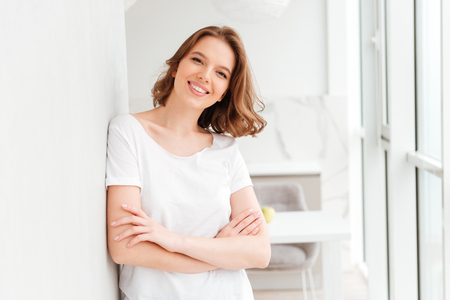 Image of happy young woman standing near window with arms crossed. Looking camera.