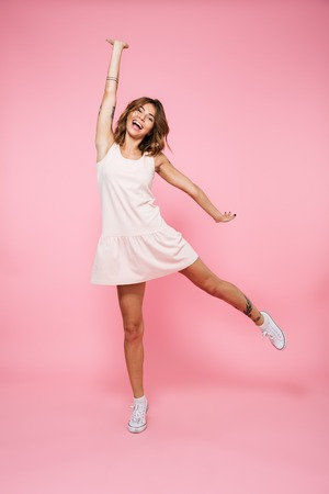 Full length portrait of a laughing joyful girl in summer dress jumping with outstretched hand and looking at camera isolated over pink background