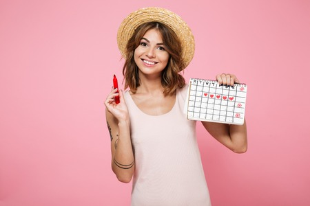 Portrait of a young smiling girl in summer hat checking her periods with a calendar and a felt-tip pen isolated over pink background Stockfoto