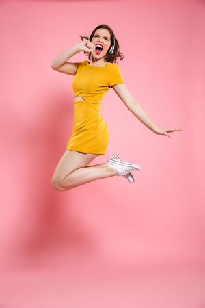 Full length portrait of pretty young woman in headphones having fun while listening to music, isolated over pink background