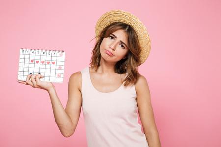 Portret van een droevig ongelukkig meisje in de zomerhoed die haar periodekalender houdt en camera bekijkt die over roze achtergrond wordt geïsoleerd Stockfoto