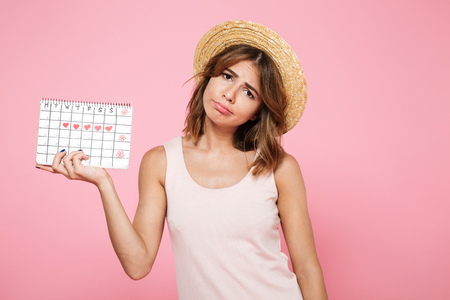 Portrait of a sad unhappy girl in summer hat holding her periods calendar and looking at camera isolated over pink background