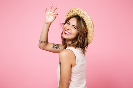 Portrait of a funny young girl in summer hat looking at camera over shoulder and playing with chewing gum isolated over pink background