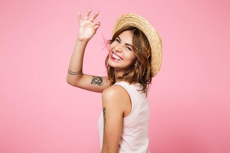 夏帽子の肩越しにカメラ目線とピンク背景に分離されたガムで遊ぶの面白い少女の肖像画