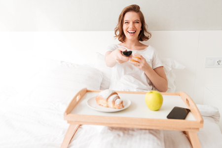 Picture of smiling young lady sitting indoors at home with croissant and juice. Looking aside watch tv holding remote control.