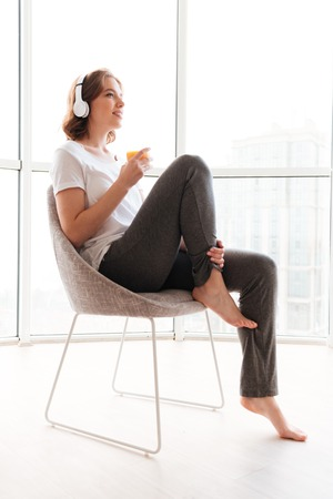 Photo of happy young woman sitting near window drinking juice listening music. Looking aside.