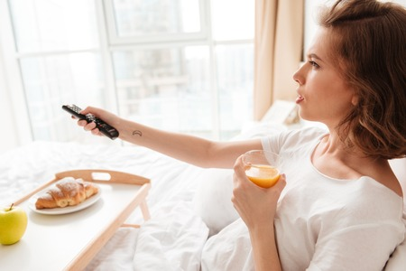 Side view picture of serious young lady sitting indoors at home with croissant and juice. Looking aside watch tv holding remote control.
