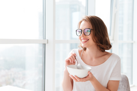 Picture image of cheerful young pretty woman sitting indoors at the table with juice and croissant eating corn flakes. Looking aside.