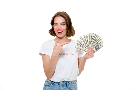 Portrait of a young playful girl holding bunch of money banknotes while pointing finger at camera and winking isolated over white background
