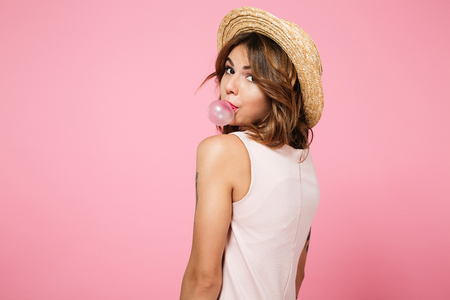 Portrait of a young pretty girl in summer hat looking at camera over shoulder and chewing bubble gum isolated over pink background