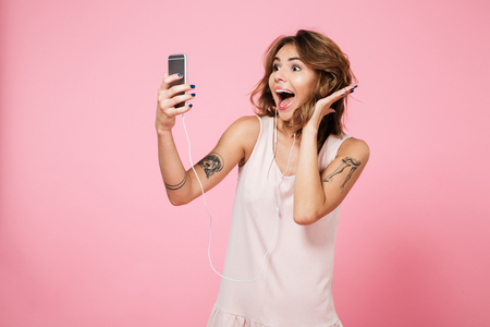 Portrait of a joyful pretty girl listening music with earphones while standing and taking a selfie with mobile phone isolated over pink background