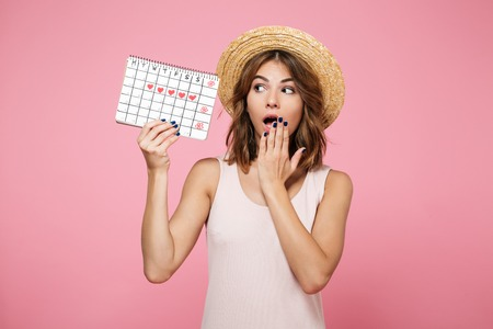 Portrait of a shocked surprised girl in summer hat holding and looking at calendar with drawn hearts isolated over pink background