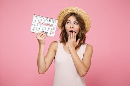 Portret zszokowanej, zaskoczonej dziewczyny w letnim kapeluszu, trzymając i patrząc na kalendarz z narysowanymi sercami na białym tle nad różowym tłem Zdjęcie Seryjne