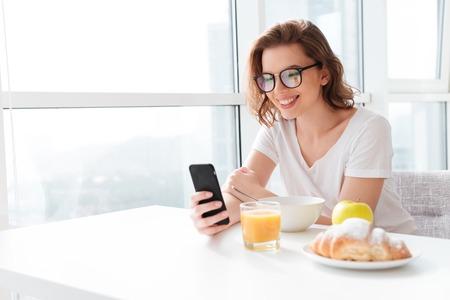 Zdjęcie wesołej młodej niesamowitej kobiety siedzącej w pomieszczeniu przy stole z sokiem i rogalikiem i płatkami kukurydzianymi. Pomijając rozmowy przez telefon komórkowy.