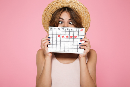 Portrait of a crazy funny girl in summer hat holding and hiding behind a periods calendar isolated over pink background