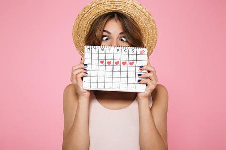 Portret van een gek grappig meisje in de zomerhoed die die en achter een periodekalender houden verbergen zich over roze achtergrond wordt geïsoleerd