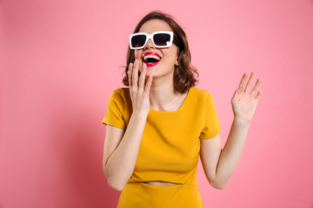 Portrait of a happy young woman in sunglasses and dress standing and laughing isolated over pink background