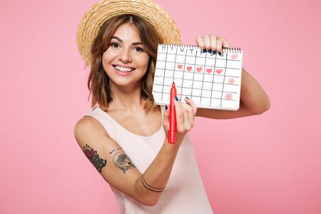 Portret uśmiechniętej ładnej dziewczyny w letnim kapeluszu sprawdzającej miesiączki zgodnie z kalendarzem za pomocą flamastra na białym tle na różowym tle