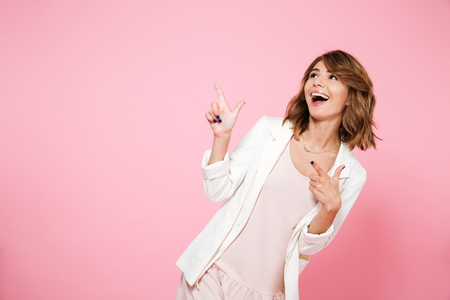 Portrait of a happy smiling girl in summer dress pointing finger away at copy space isolated over pink background