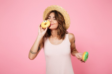 Portrait of a lovely cute woman in summer hat holding and smelling donuts isolated over pink background
