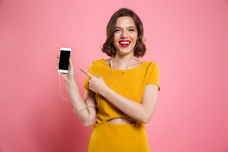 Portrait of a happy woman in earphones listening to music while standing and pointing finger at blank screen mobile phone isolated over pink background