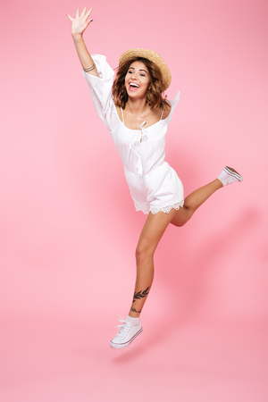 Full length portrait of a happy pleased girl in summer dress and hat jumping isolated over pink background Stockfoto