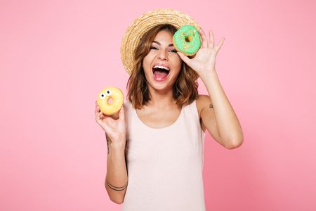 Portrait of an excited happy woman in summer hat holding donuts isolated over pink background