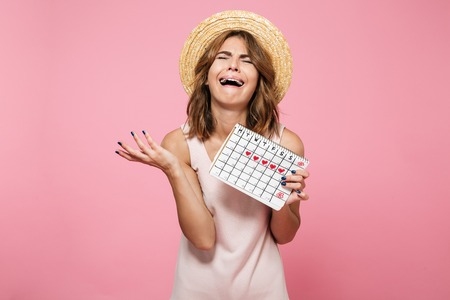 Portrait of an upset desperate girl in summer hat holding calendar with drawn hearts and crying isolated over pink background