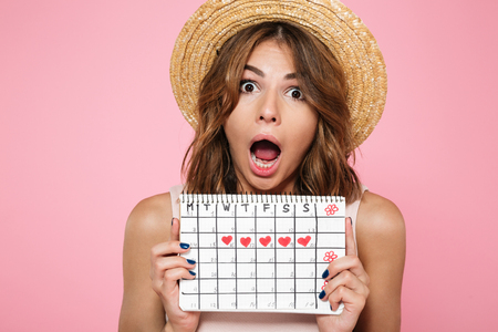 Portrait of a crazy young girl in summer hat holding her menstruation calendar and screaming isolated over pink background 版權商用圖片