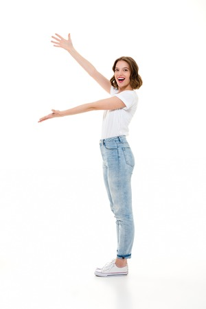 Picture of cheerful pretty caucasian lady standing isolated. Looking camera gesturing with hands showing copyspace. Stock Photo