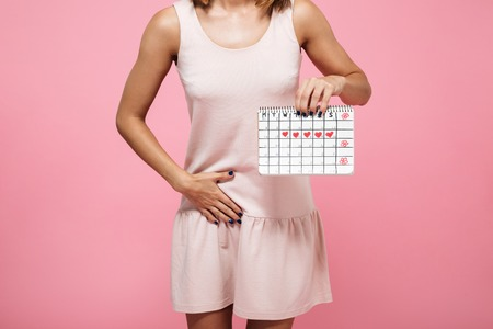 Cropped image of a young woman in dress holding periods calendar and touching her belly isolated over pink background