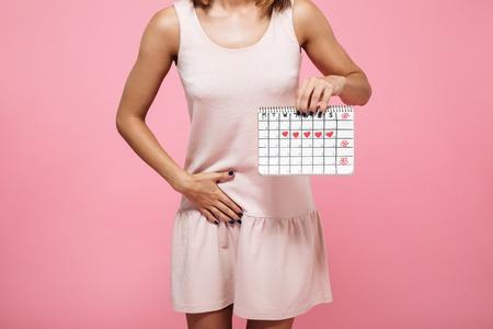 Imagen recortada de una mujer joven en vestido con calendario de períodos y tocando su vientre aislado sobre fondo rosa