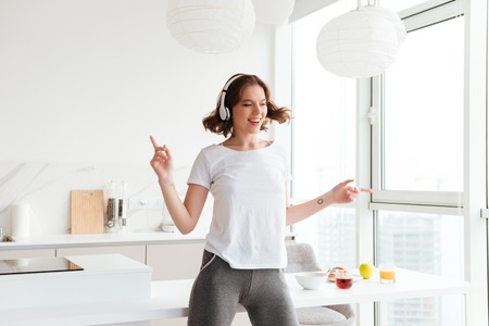 Photo of cheerful young woman dancing listening music. Looking aside.
