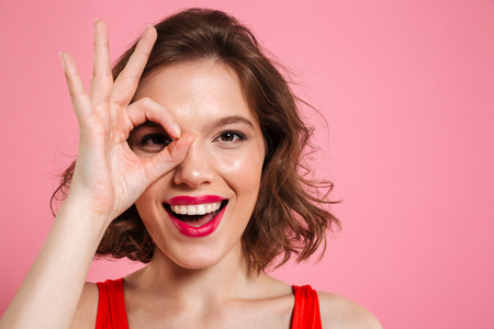 Close-up portrait of young happy girl with red lips looking at camera through OK sign, isolated on pink background