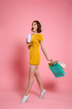 Full length photo of cute amazed woman in yellow dress holding drink and colorful shopping bags, looking aside, isolated on pink background
