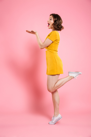 Full length portrait of playful attractive woman in yellow dress standing on one leg, showing empty palm, isolated on pink background Stock fotó