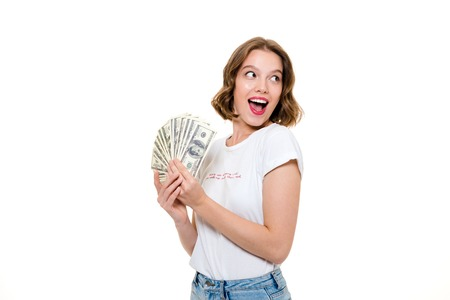 Close up portrait of a joyful young girl holding bunch of money banknotes and looking away at copy space isolated over white background Stok Fotoğraf