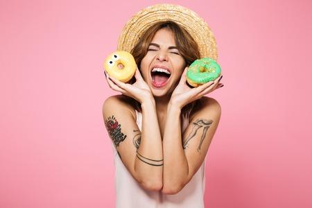 여름 모자 도너츠 잡고 웃고 분홍색 배경 위에 격리 된 행복 흥분된 여자가 세로
