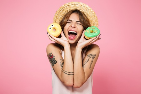 Portrait of a happy excited girl in summer hat holding donuts and laughing isolated over pink background
