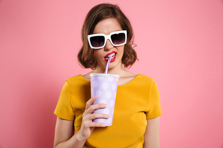 Portrait of a girl in sunglasses holding cup with drink and looking at camera isolated over pink background