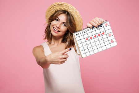 Portrait of an happy pretty girl in summer hat pointing finger at a calendar with drawn hearts isolated over pink background