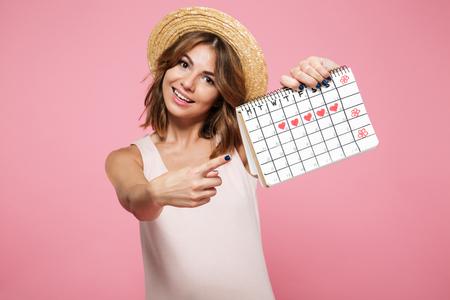 Portret szczęśliwa ładna dziewczyna w kapeluszu lato wskazując palcem na kalendarz z narysowanymi sercami na białym tle na różowym tle