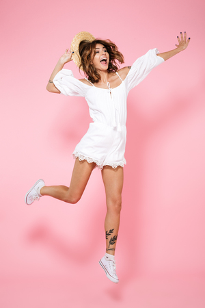Full length portrait of a joyful satisfied girl in summer dress and hat jumping isolated over pink background